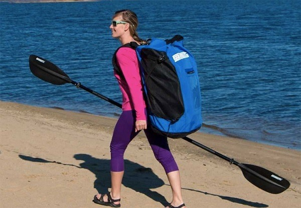 Woman carrying an inflatable kayak packed in a backpack.