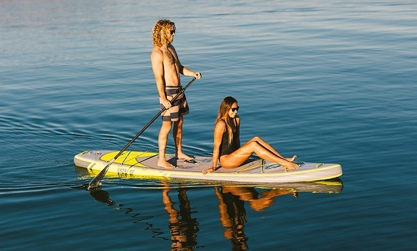 Man and woman paddle boarding.